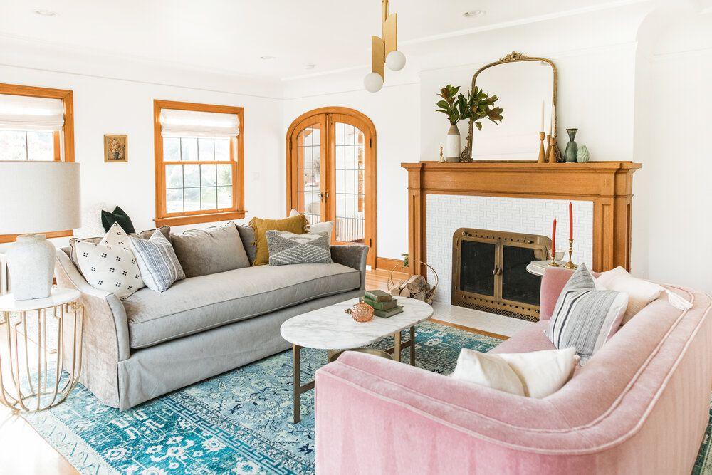 Eclectic living room features pastel colors, art deco pendant light, mirror above mantel