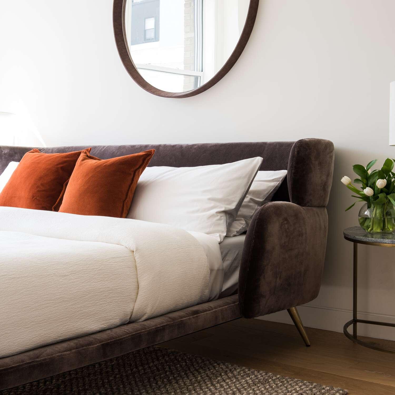 A midcentury modern bedroom with a striking velvet bed