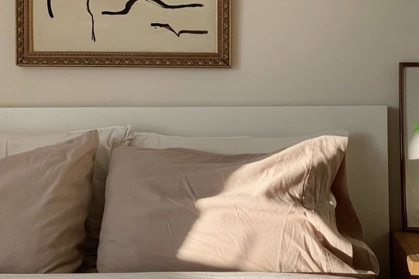 A neutral bed with abstract art above.