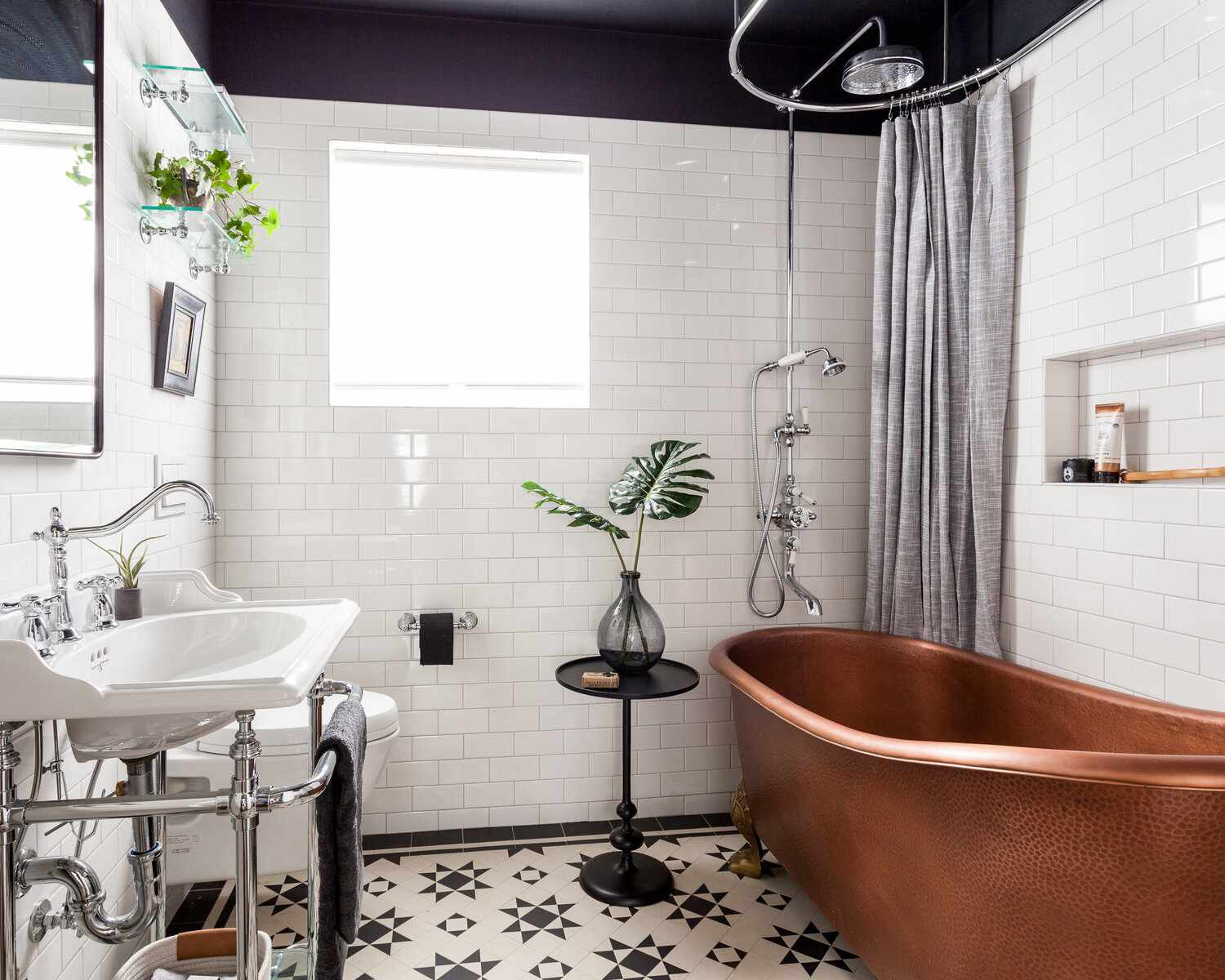 A statement-making small primary bathroom with boldly tiled floors, a copper clawfoot tub, and several glass shelves