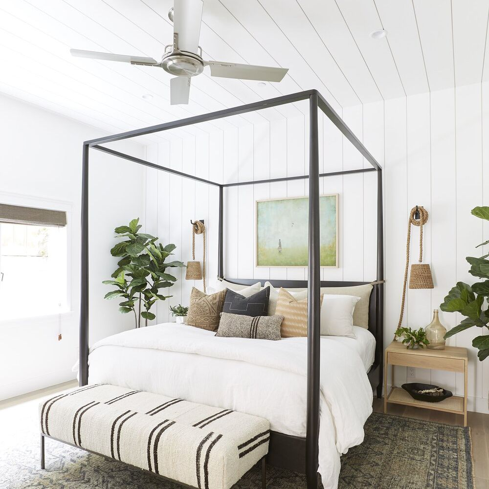 A white bedroom with a black canopy bed