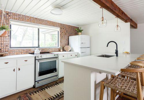 kitchen with terracotta tiles and white fridge