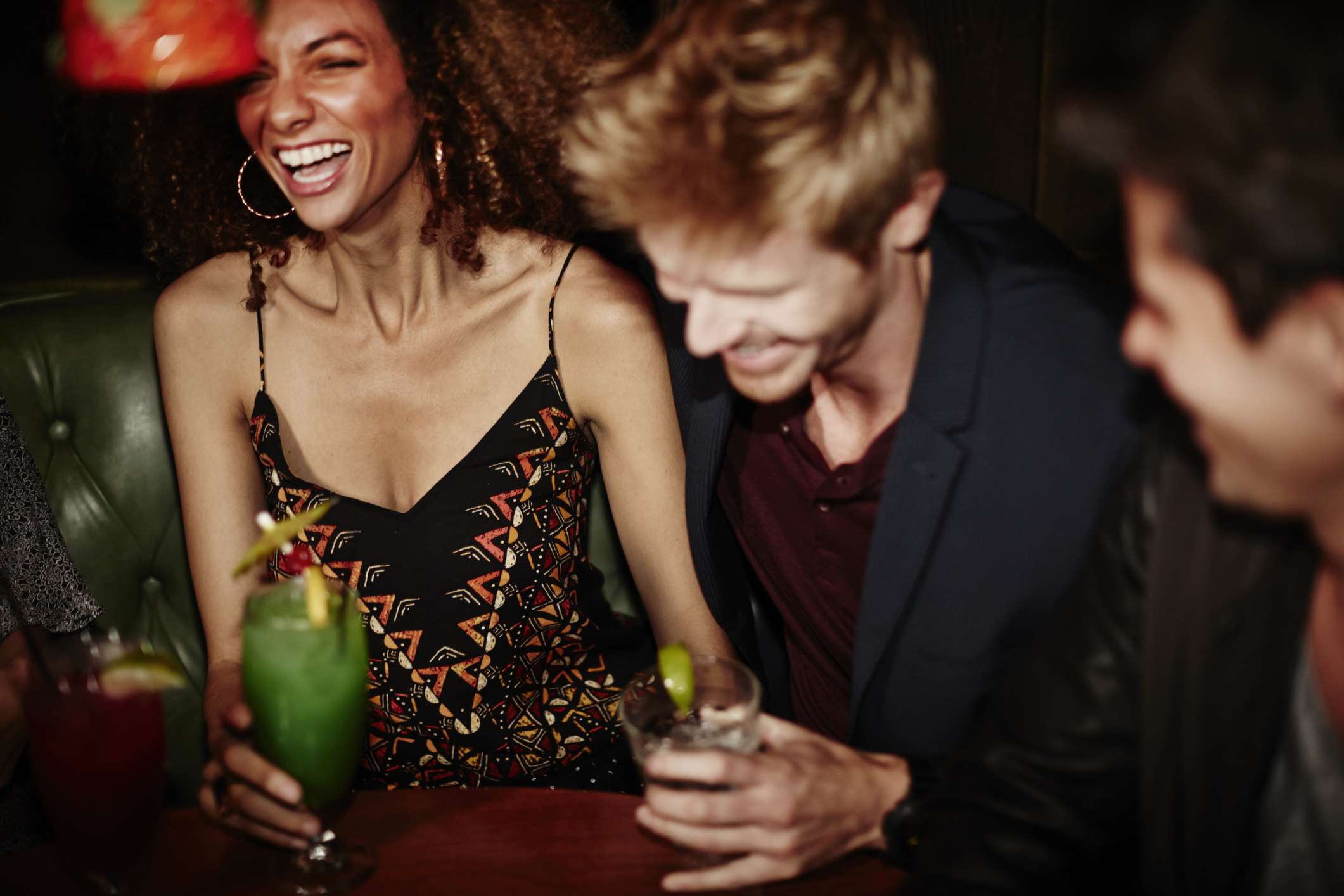 Young people laughing with cocktails in hand