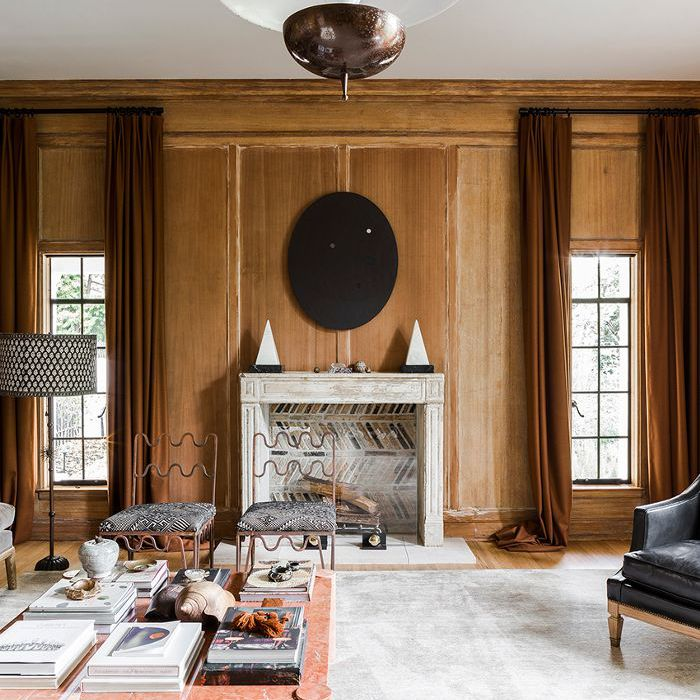 Oblong windows with long brown curtains flanking fireplace