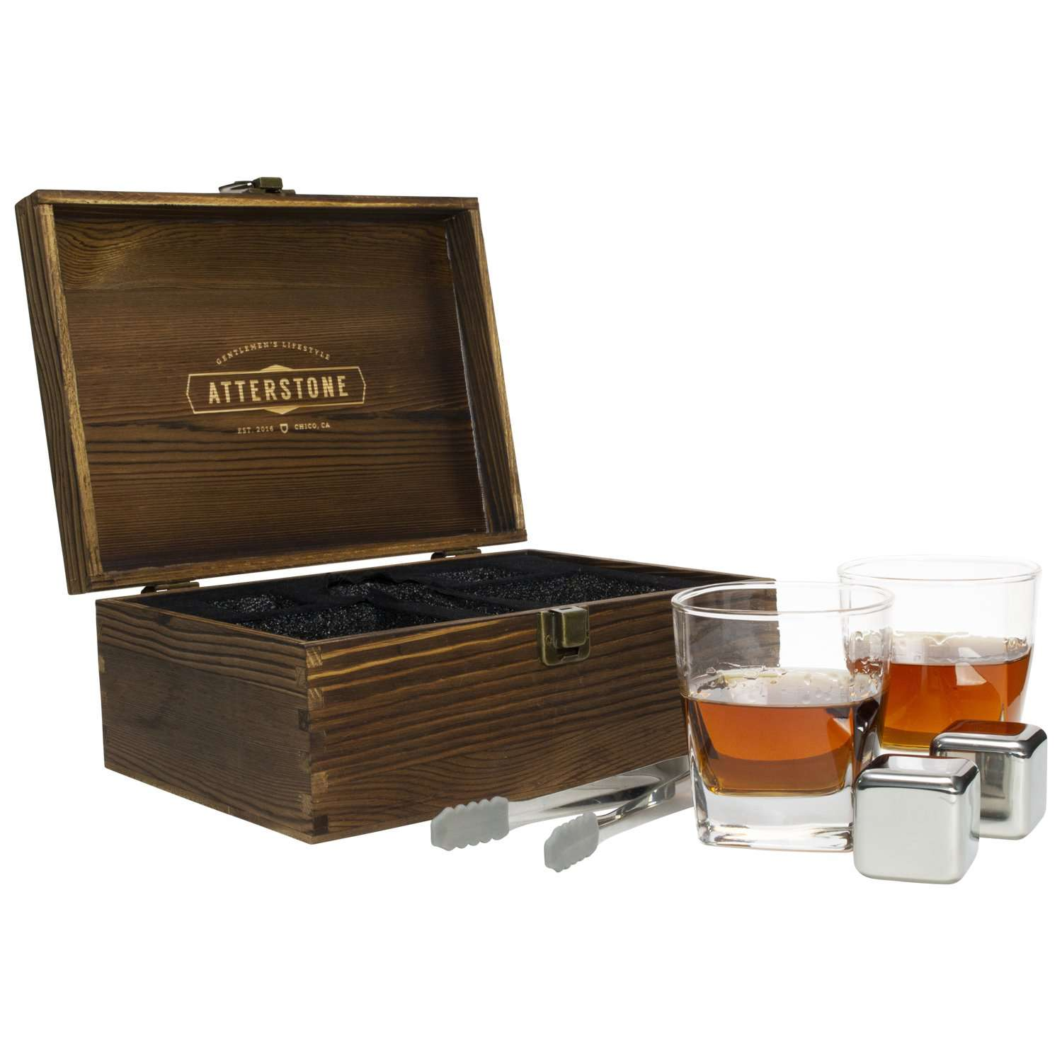 A wooden box beside a pair of tongs, two whiskey glasses, and two metal whiskey stones.