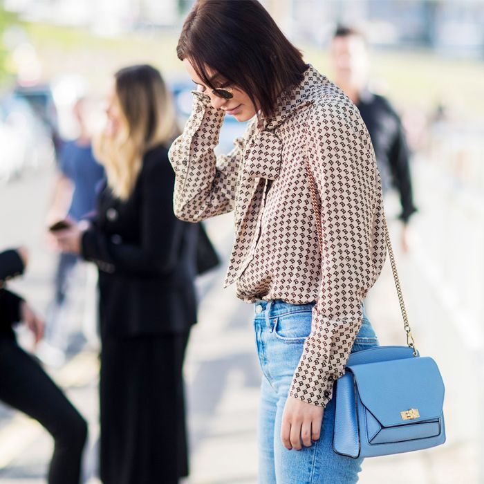 A woman wearing a long-chained blue crossbody bag..