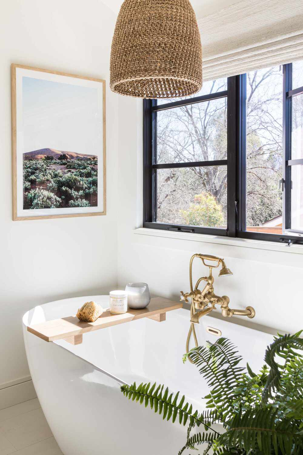 A freestanding bathtub topped with a bath tray