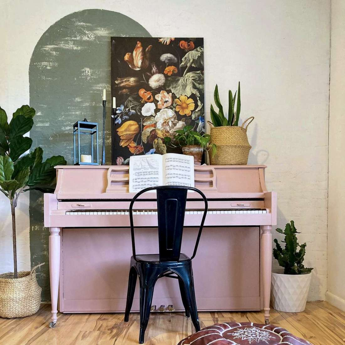 painted white brick wall with green oval painted over, pink piano against wall