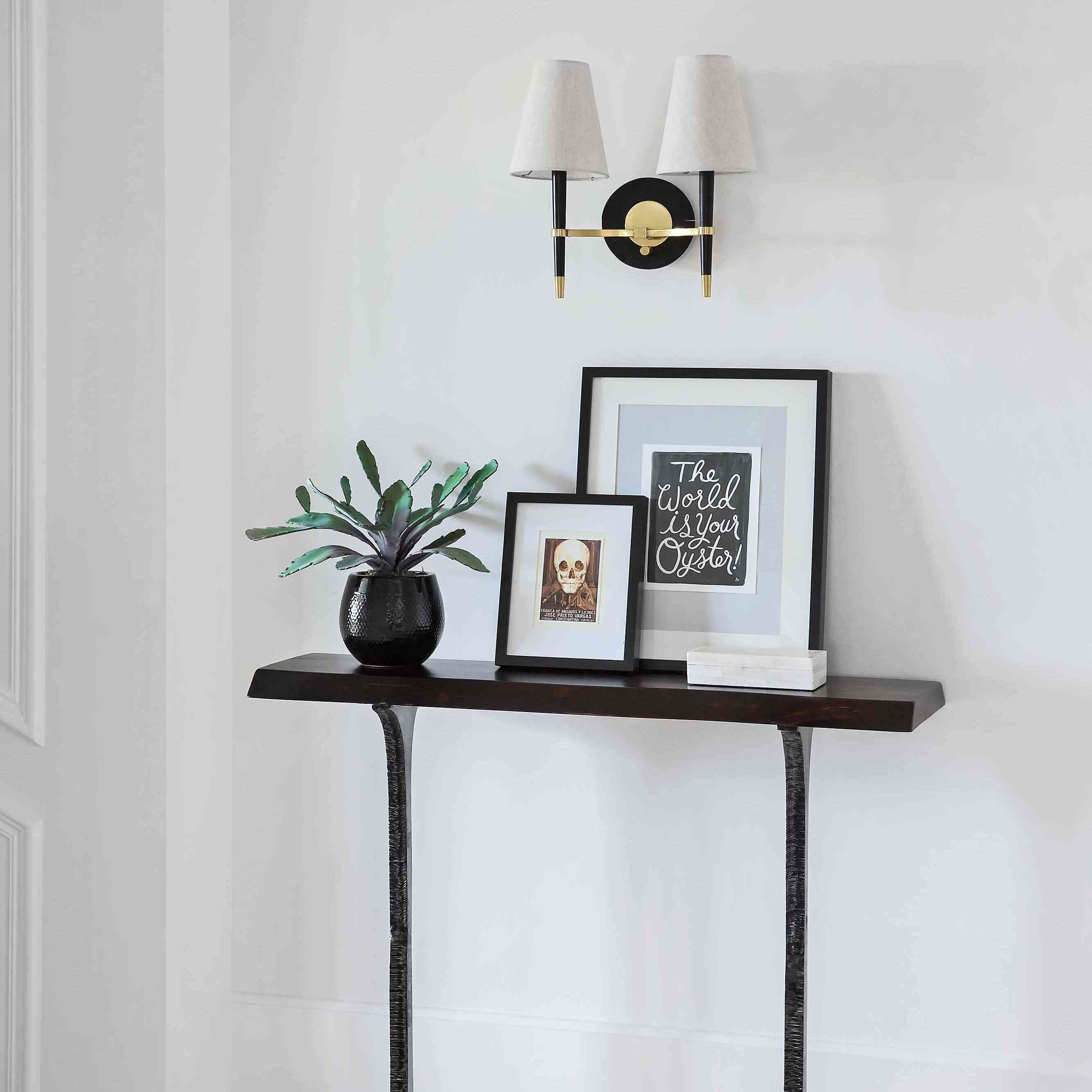 Styled console features a plant, framed art, sconce lighting