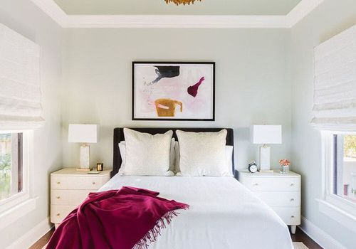 Centered bed with chandelier and burgundy throw draped at corner of bed