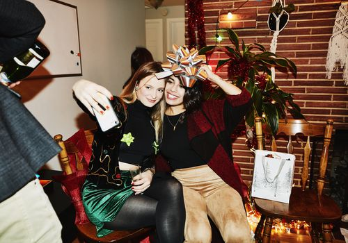 Two young women take selfie at holiday party