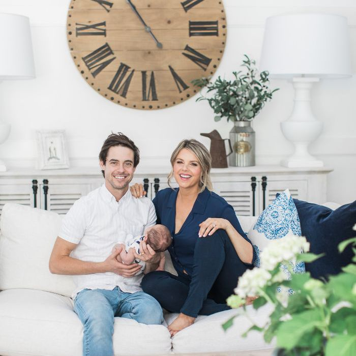Bachelorette Ali Fedotowsky Home Tour: Ali and husband Kevin hold their newborn child and are seated on their white couch