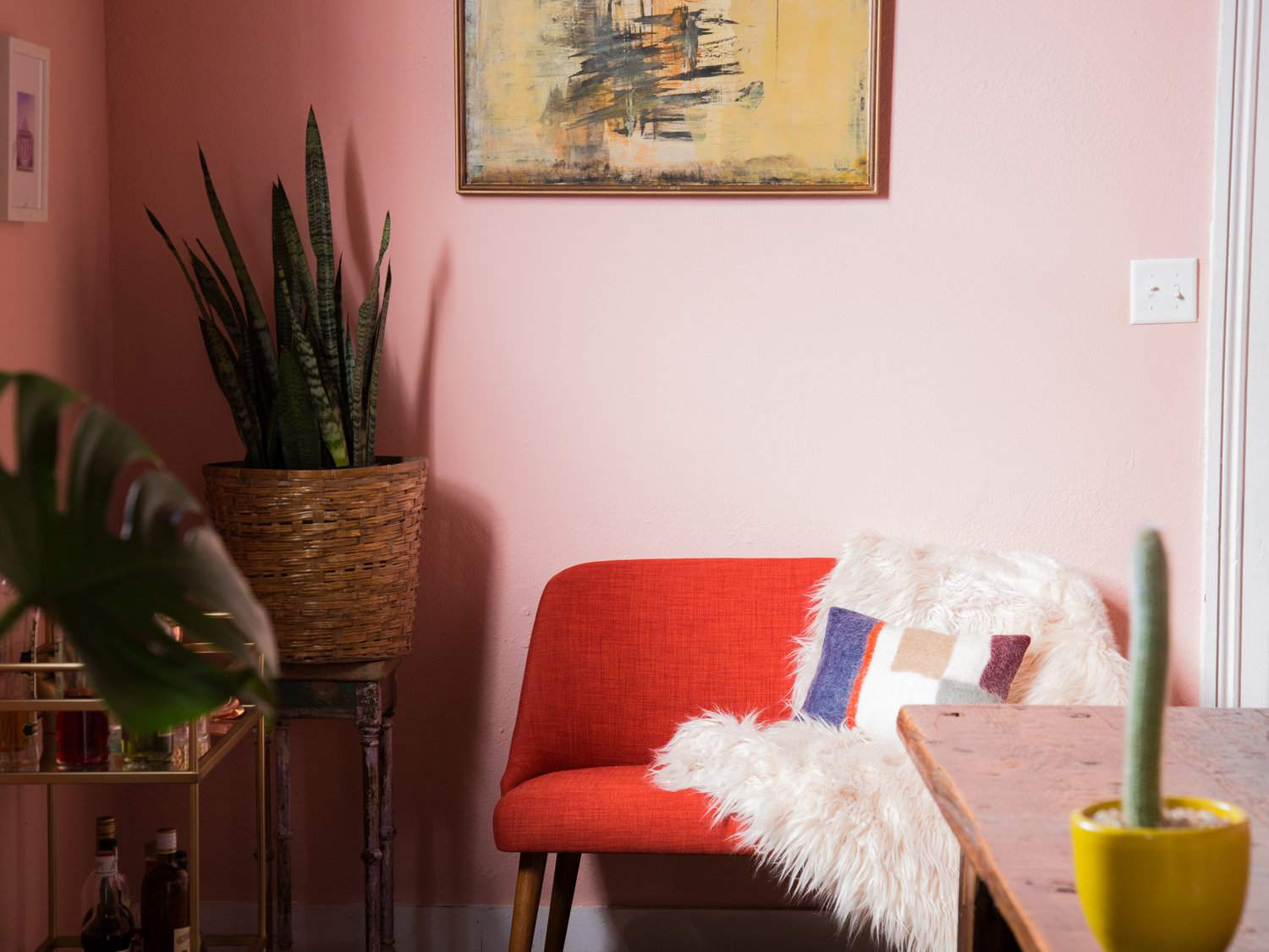 pink dining room with red seating gold barcart