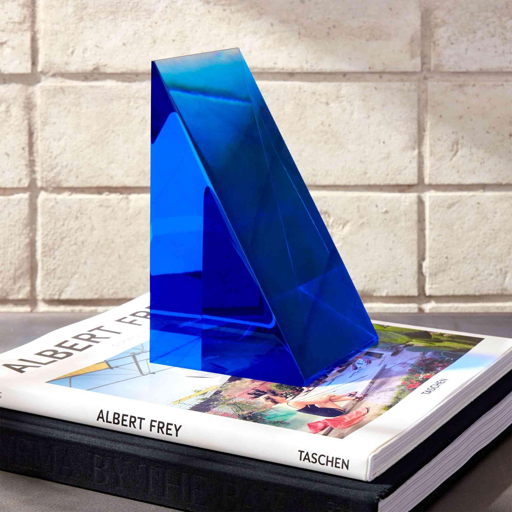 A triangular blue acrylic bookend by CB2.