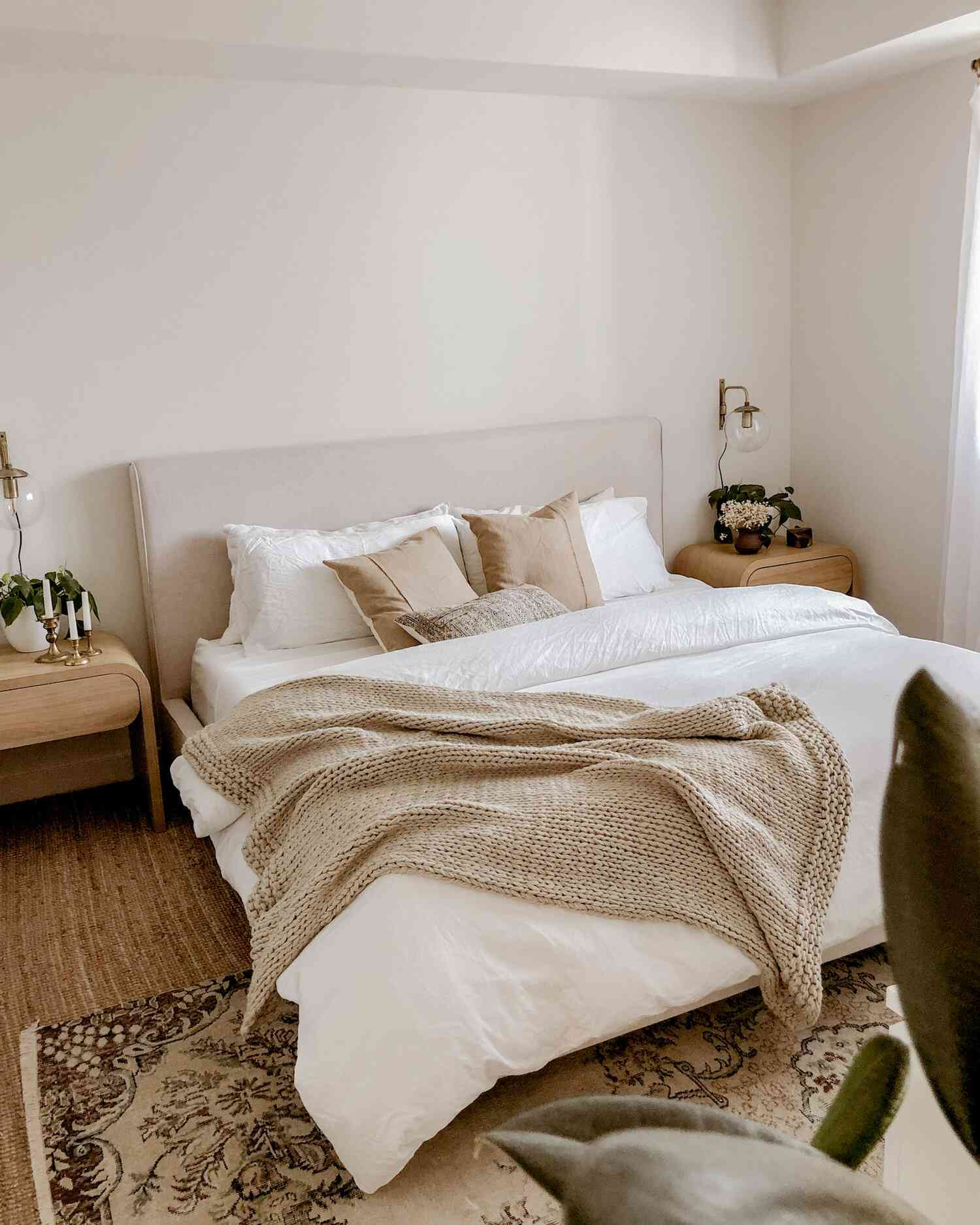 Soft neutral bedroom with white comforter and beige knit blanket.