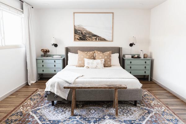 Neutral bedroom with sage green nightstands.