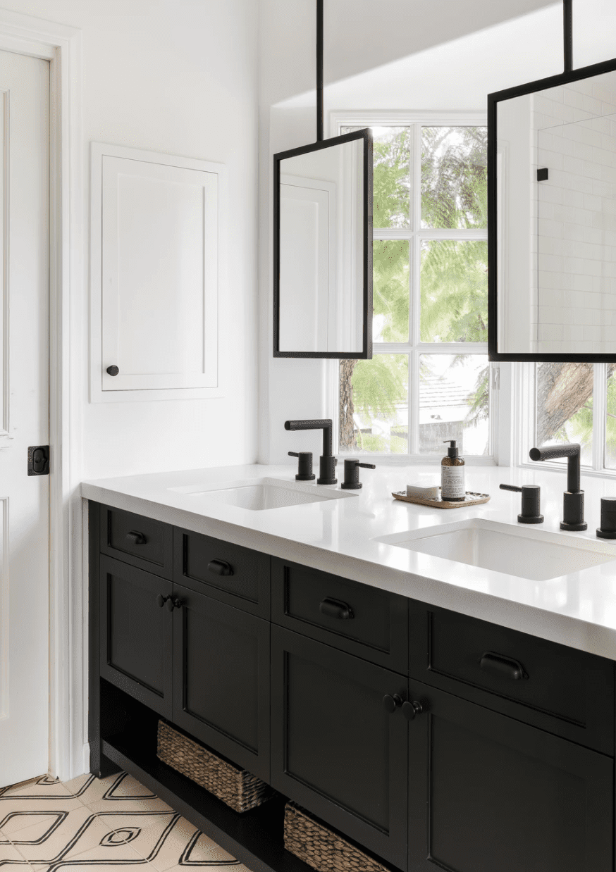 A small bathroom vanity situated against a window, with two hanging mirrors draped in front of the window