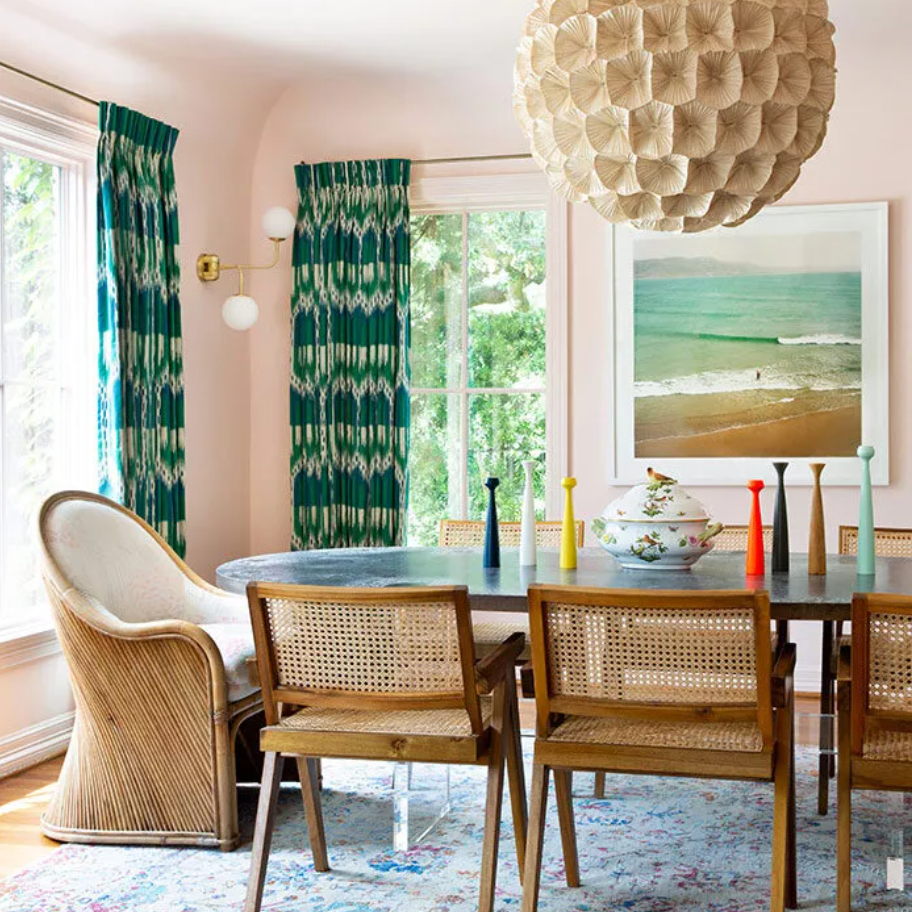 A dining room with light pink walls, a light blue rug, and vibrant green printed curtains