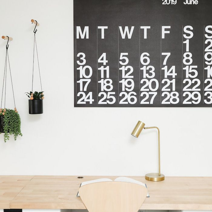 white and wooden desk with large black and white calendar hanging on the wall next to two small hanging plants