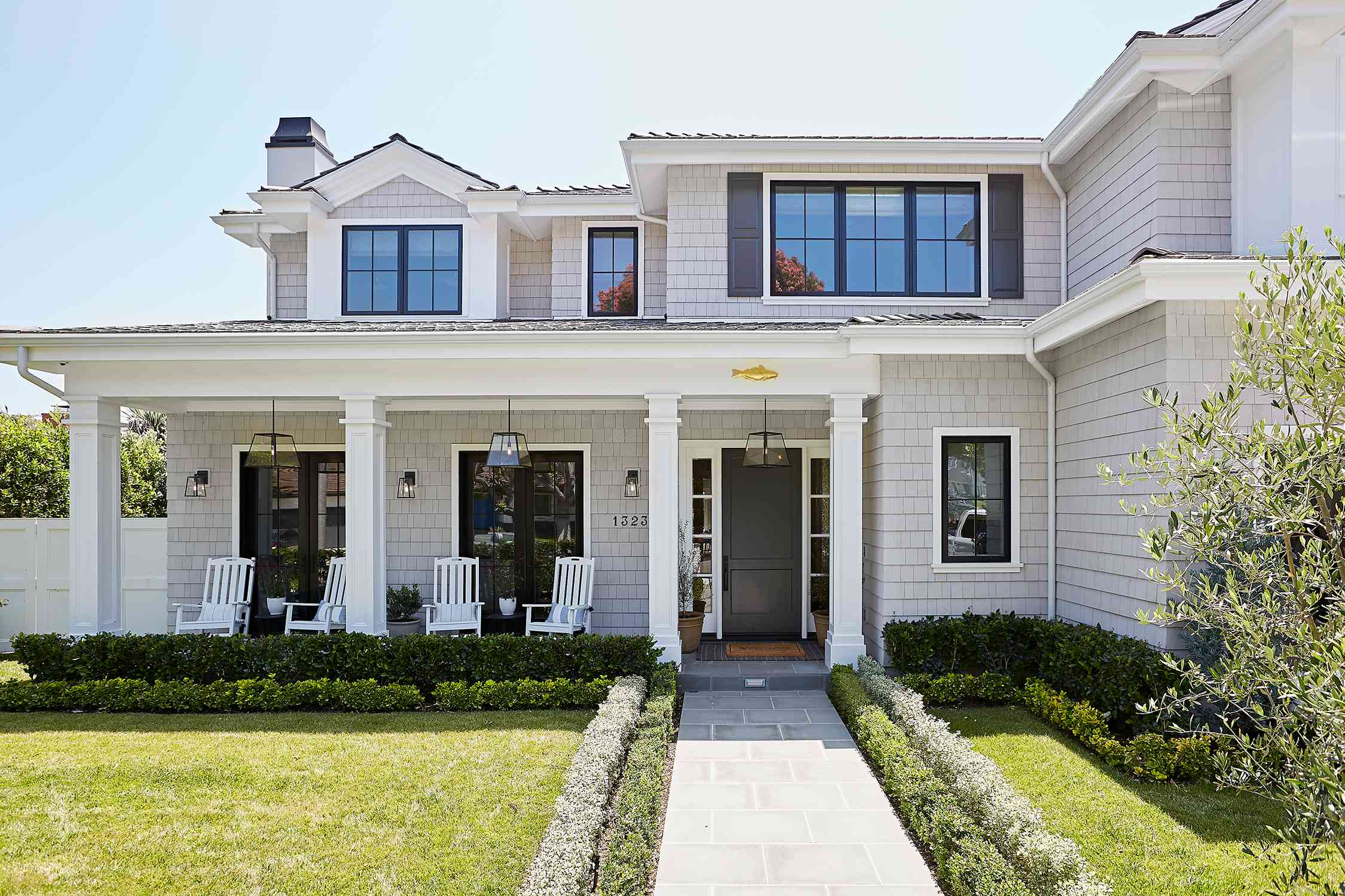 Exterior home with line of short shrubbery leading to front door.