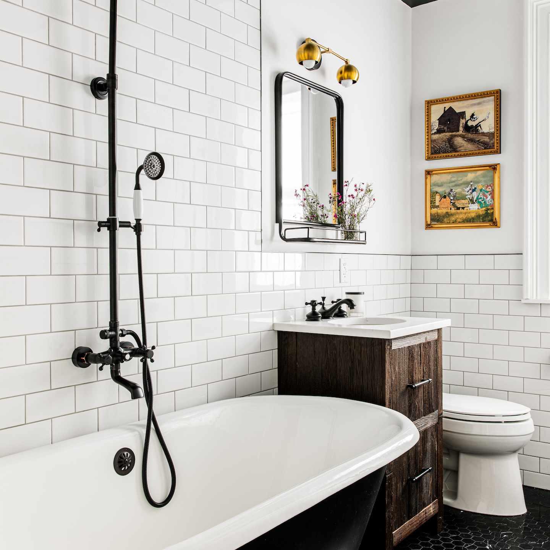Cast iron bathtub in all-white subway tiled bathroom.
