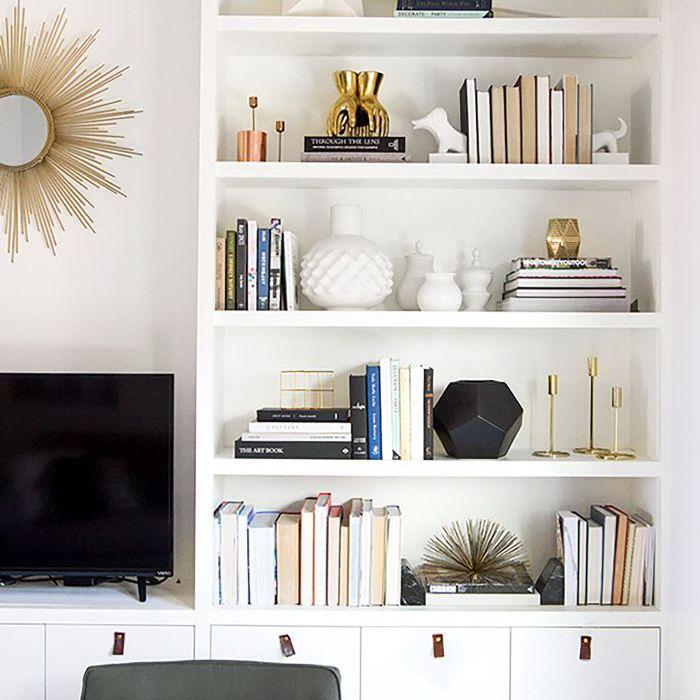 Sala de estar blanca con estantes incorporados diseñados con libros y objetos blancos.