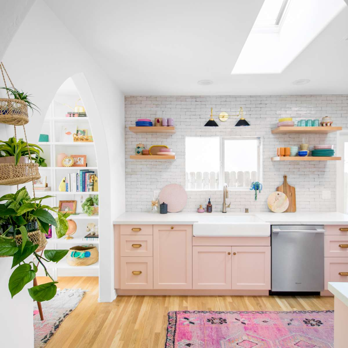 Kitchen with plants and pink cabinets.
