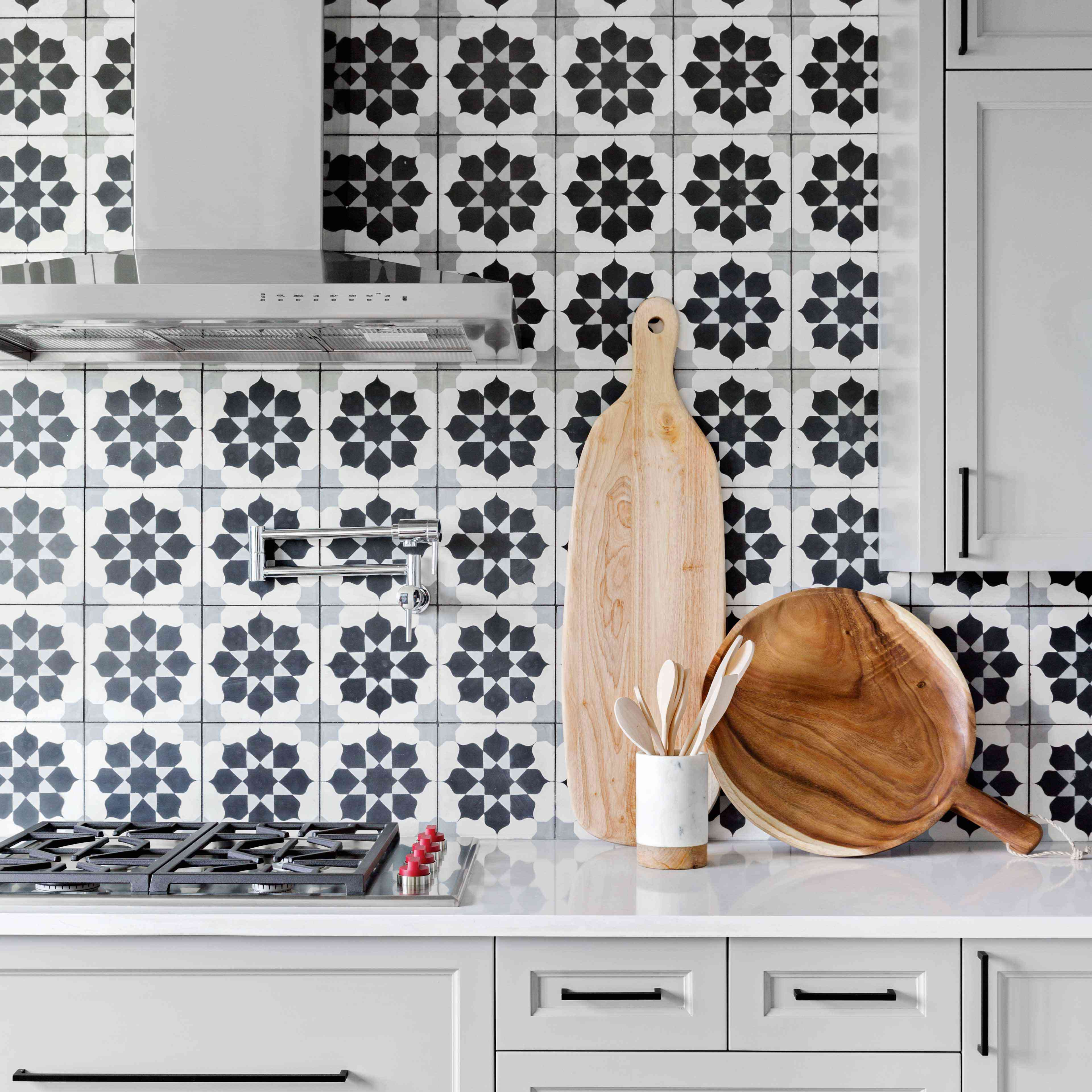 A kitchen with gray cabinets and a boldly tiled backsplash