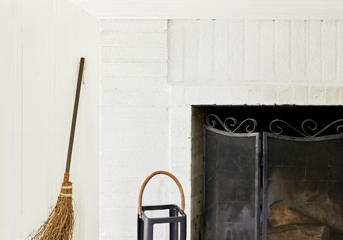 target halloween decorations - white fireplace with spooky decor and broom