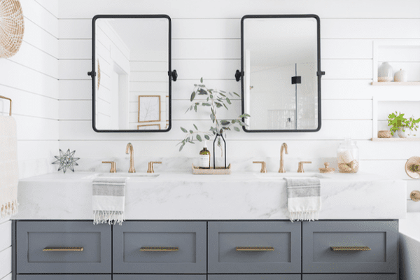 A blue-gray double vanity with black-rimmed mirrors