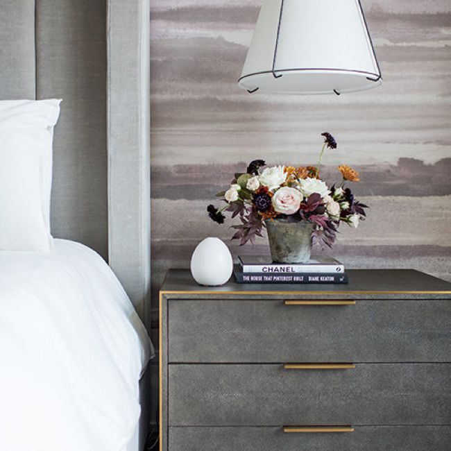 Bedroom with grey bed and nightstand and purple watercolor wallpaper