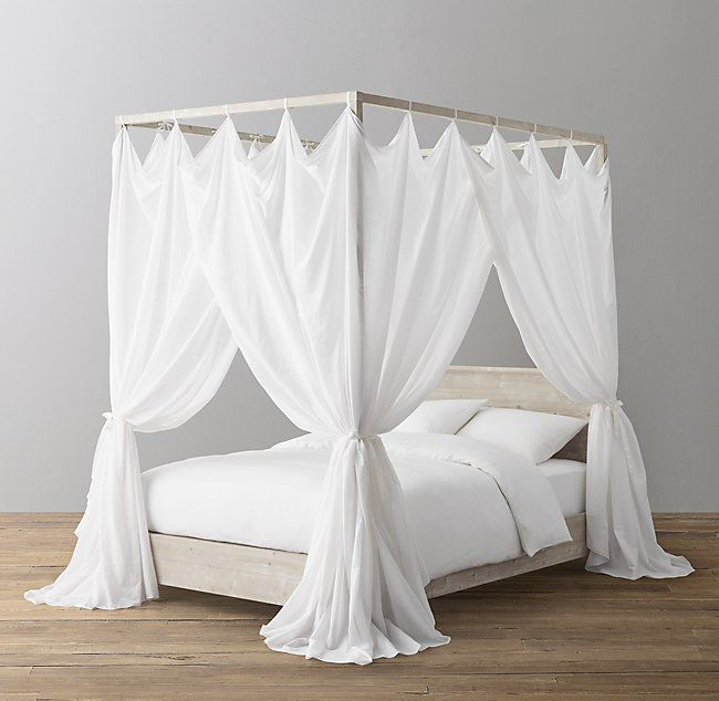 A four poster bed with a sheer white bed canopy hanging on it.