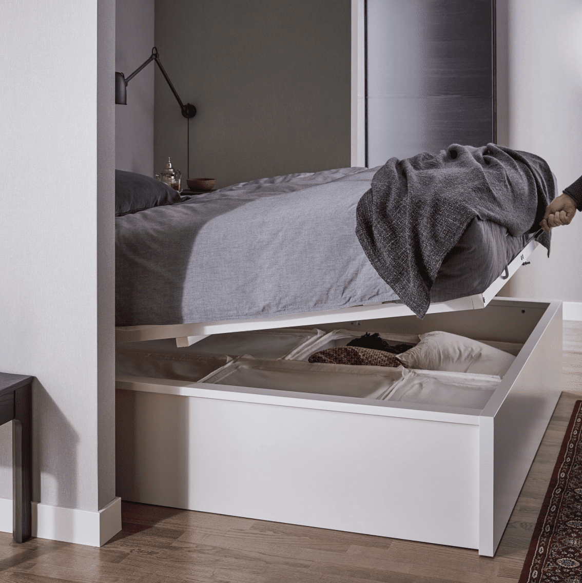 A white platform bed that hinges to reveal storage underneath, which is currently for sale at IKEA