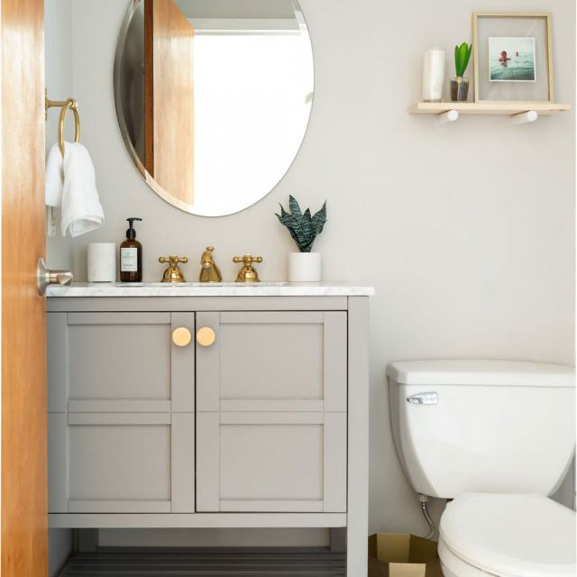 Powder room with oval mirror.