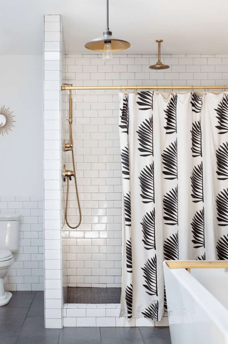 A small primary bathroom with a bold printed shower curtain