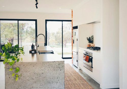Large concrete island in white kitchen.