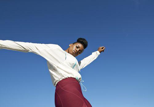 Mujer joven en ropa deportiva contra un cielo claro y soleado