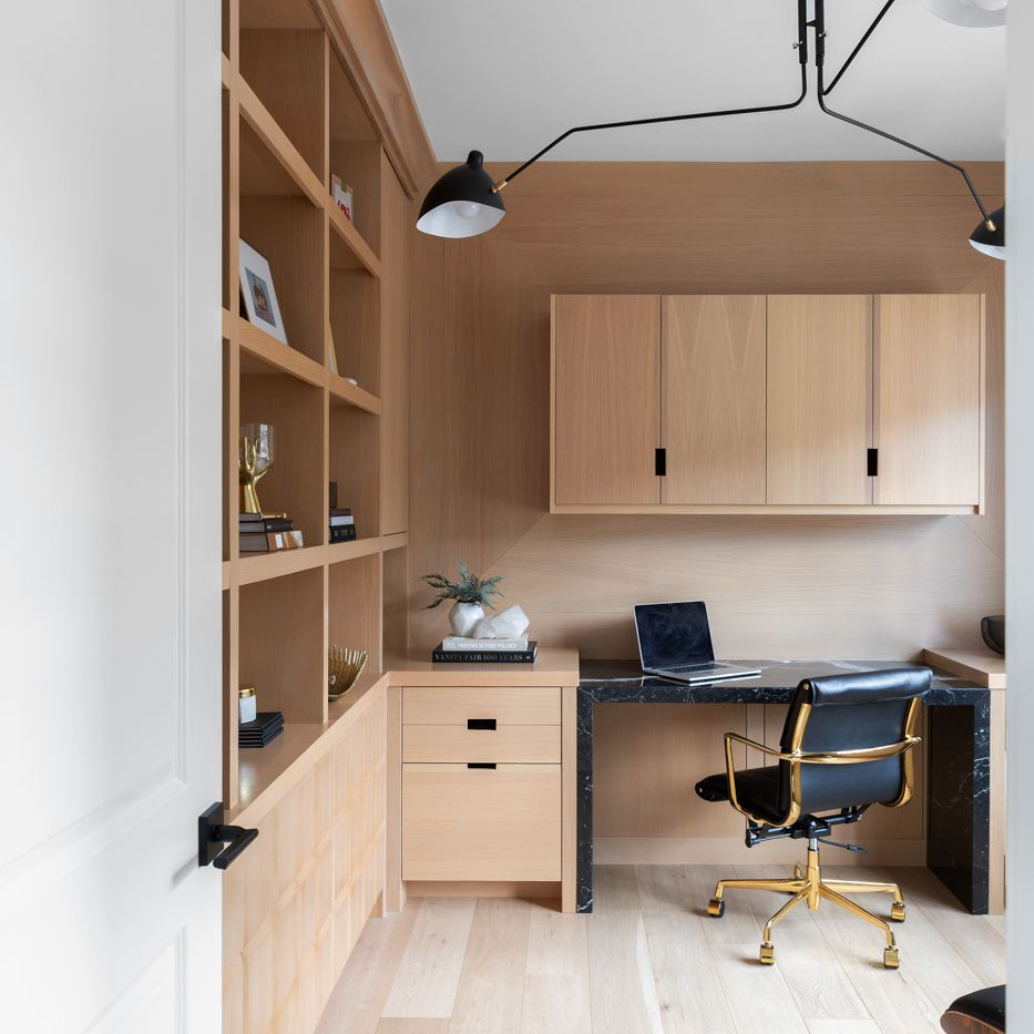 A home office lined with ceiling-to-floor wooden shelves and matching hardwood floors