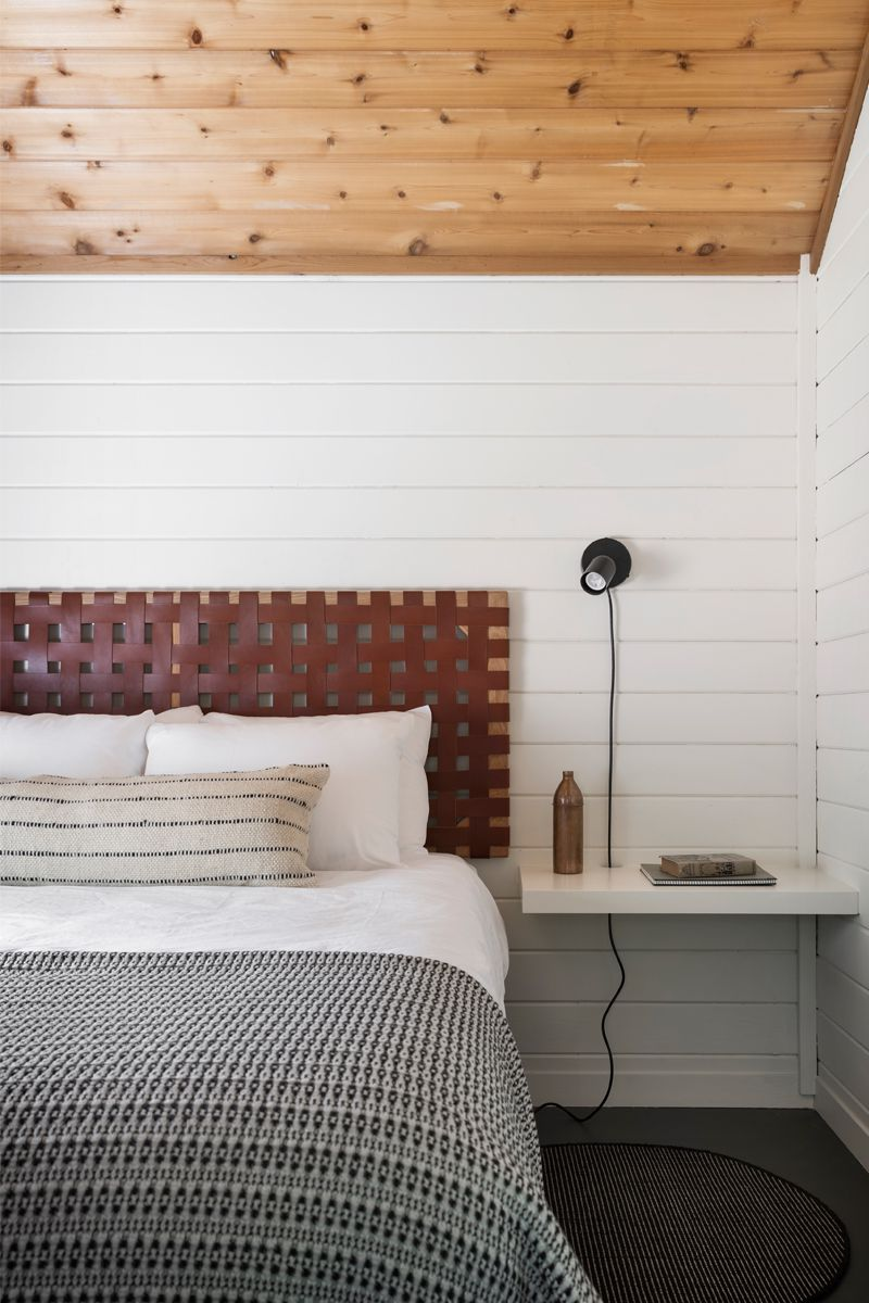 Rustic bedroom with white shiplap walls.