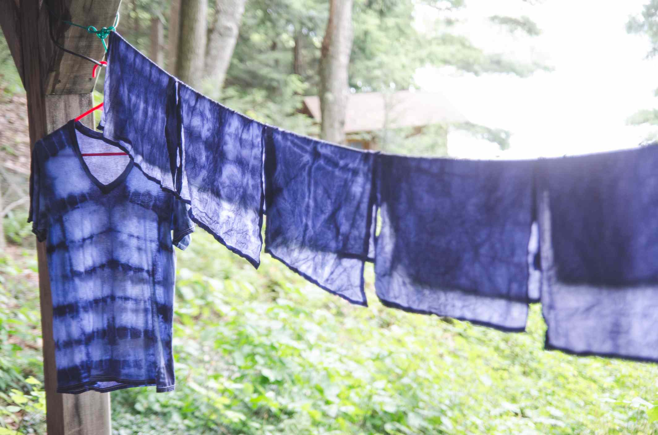Indigo tie dyed t-shirt and napkins hang on clothesline outdoors