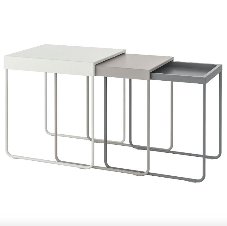 A set of three nesting tables in white, taupe, and gray.