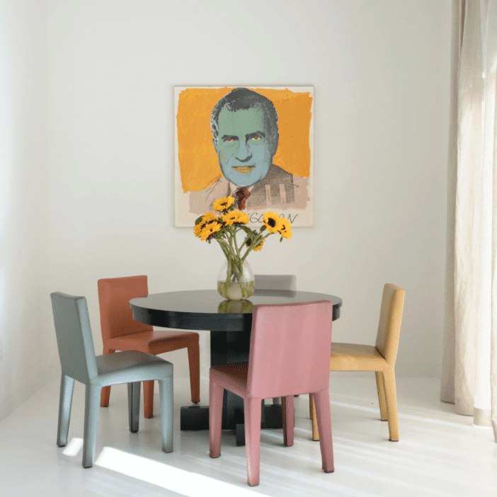A small dining room table surrounded by colorful chairs