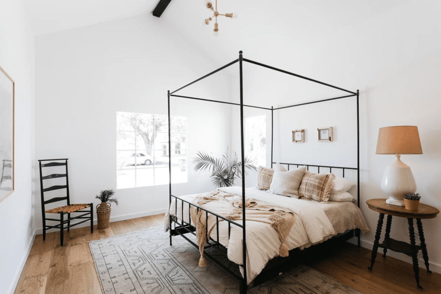 A modern bohemian bedroom with a geometric chandelier and bold ceramic table lamp