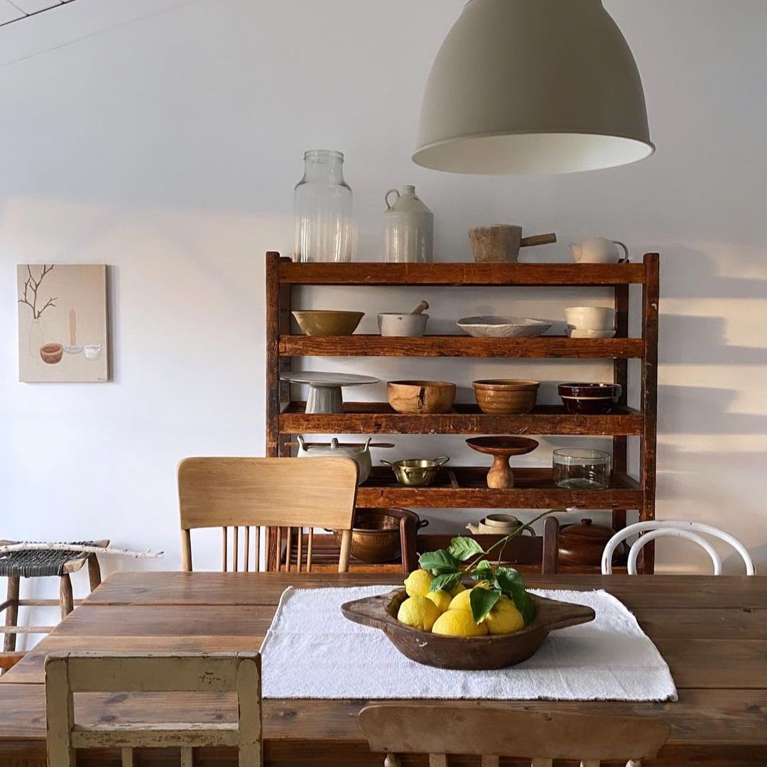 Country kitchen with mismatched antique chairs and shelves displaying antique dishes