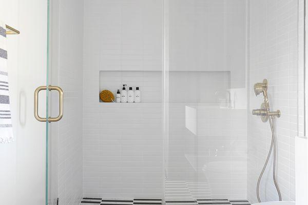 walk-in shower with patterned tile floor
