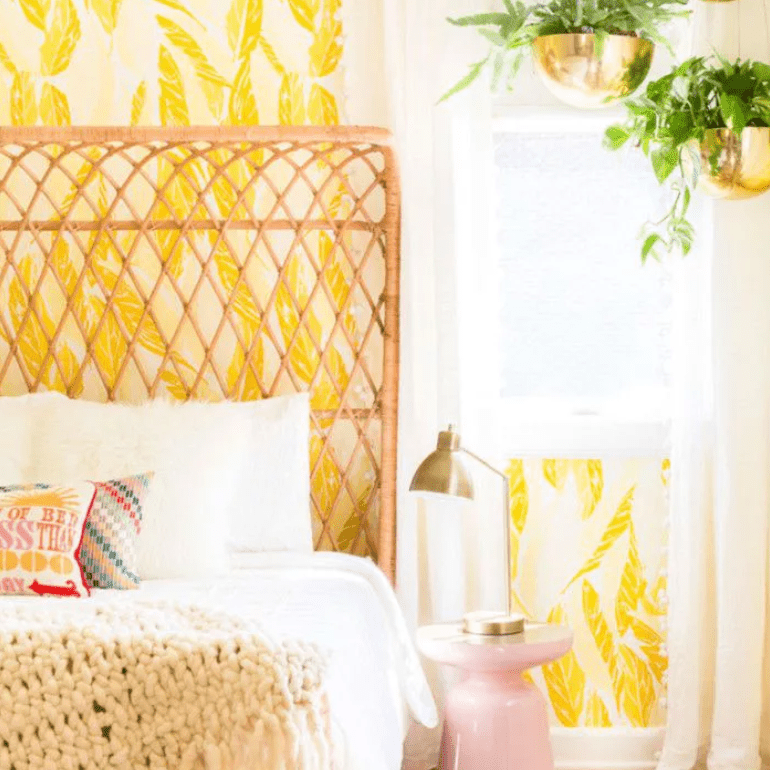 Whimsical bedroom with rattan headboard and yellow feather patterned wallpaper.