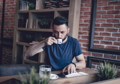 man sipping coffee with books open