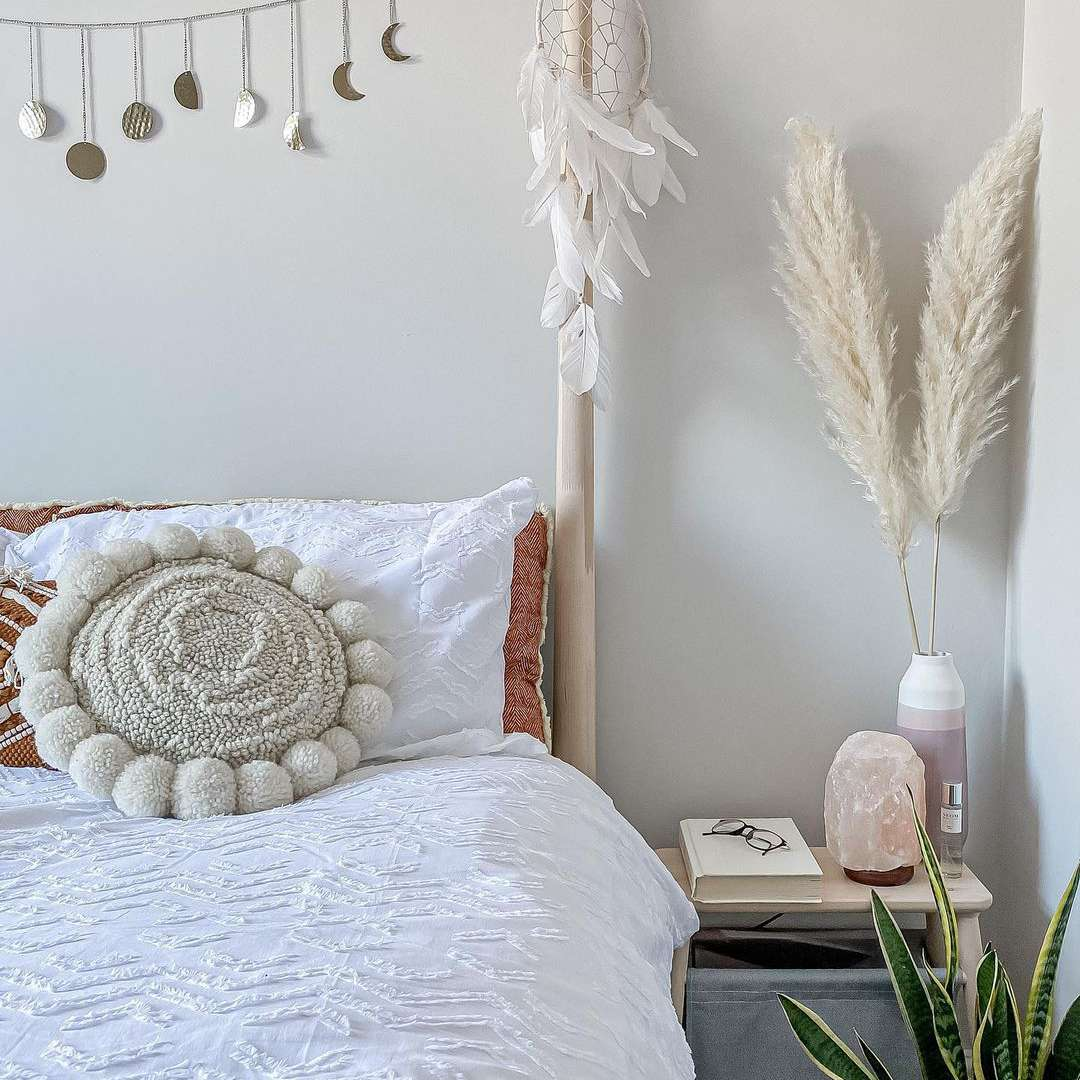 Boho bedroom with dream catcher and pampas grass.