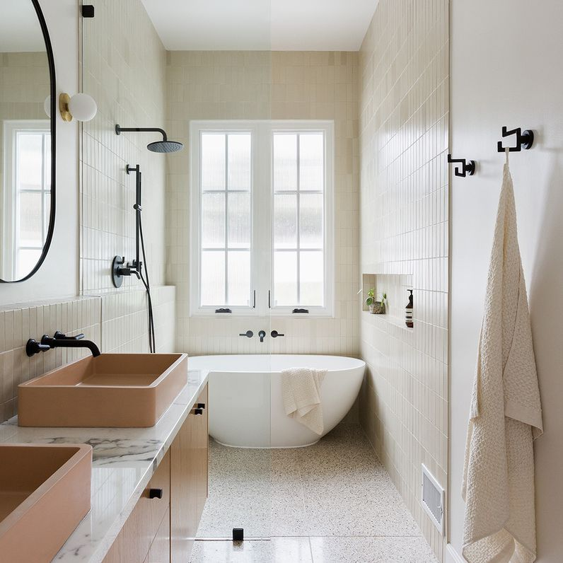 Modern bathroom with peach and cream color scheme and black accents