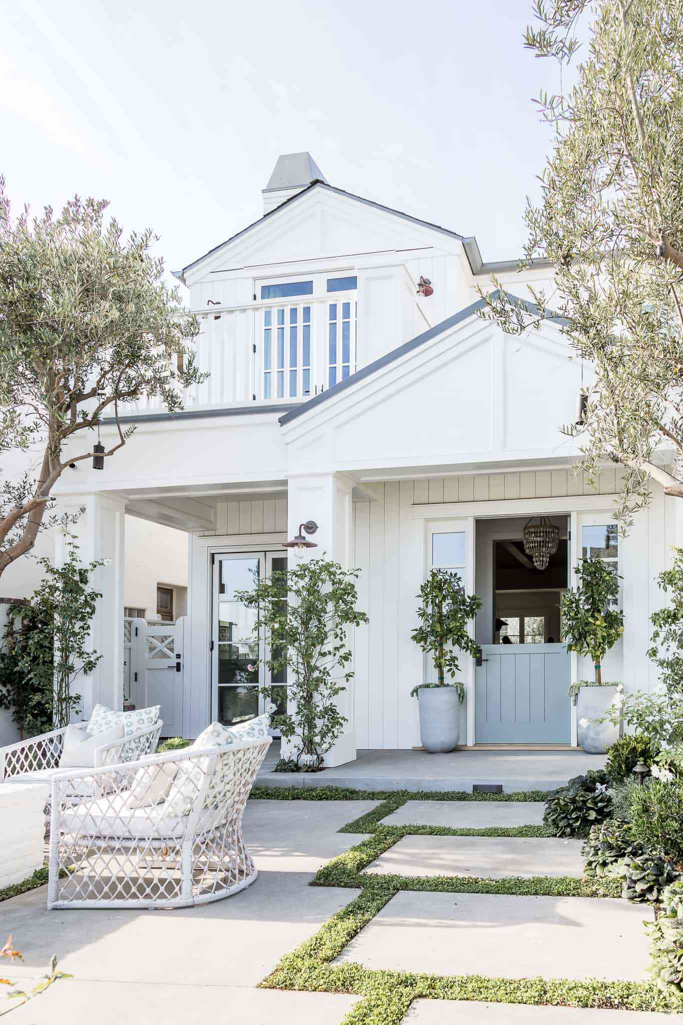 White exterior home with large tile walkway.